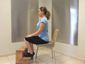 assis avec un coussin sous les fesses les pieds posés